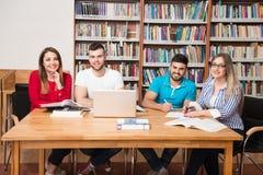 Gruppo di studenti con il computer portatile in biblioteca Fotografia Stock Libera da Diritti