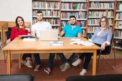 Gruppo di studenti con il computer portatile in biblioteca Fotografia Stock
