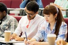 Gruppo di studenti con scrittura del caffè sulla conferenza Immagini Stock