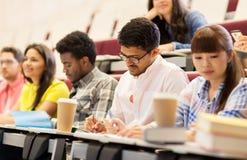 Gruppo di studenti con scrittura del caffè sulla conferenza Immagine Stock