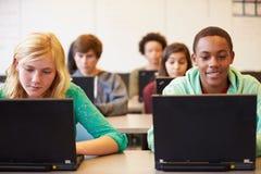 Gruppo di studenti della High School nella classe facendo uso dei computer portatili fotografia stock libera da diritti