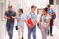 Gruppo di studenti di college che camminano lungo il corridoio immagini stock