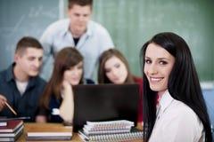 Gruppo di studenti di college che per mezzo del computer portatile Fotografie Stock