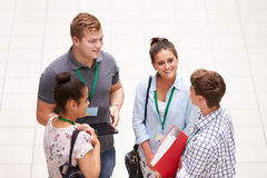 Gruppo di studenti di college che stanno nella conversazione di corridoio fotografia stock
