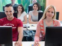 Gruppo di studenti di tecnologia nell'aula della scuola del laboratorio del computer Immagine Stock