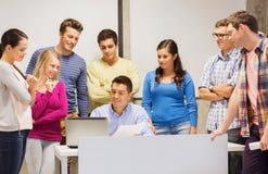 Gruppo di studenti e di insegnante con il computer portatile Fotografia Stock