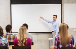 Gruppo di studenti e di insegnante sorridente in aula Fotografia Stock