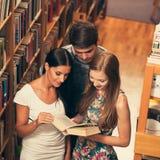 Gruppo di studenti in libri di lettura delle biblioteche - gruppo di studio Fotografia Stock