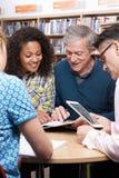 Gruppo di studenti maturi che studiano nella biblioteca Immagini Stock Libere da Diritti
