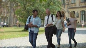 Gruppo di studenti multi-etnici e di insegnante che discutono progetto, camminante nel parco video d archivio