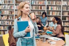 Gruppo di studenti multiculturali etnici in biblioteca Caffè bevente della ragazza bianca fotografie stock