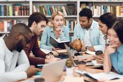 Gruppo di studenti multiculturali etnici in biblioteca Gli studenti stanno parlando e leggendo Fotografie Stock