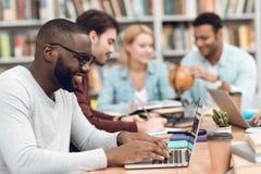 Gruppo di studenti multiculturali etnici in biblioteca Gli studenti stanno studiando Immagine Stock Libera da Diritti