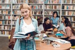 Gruppo di studenti multiculturali etnici in biblioteca Libro di lettura bianco della ragazza Fotografia Stock Libera da Diritti