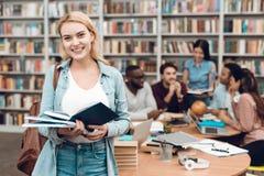 Gruppo di studenti multiculturali etnici in biblioteca Libro di lettura bianco della ragazza Immagine Stock
