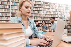 Gruppo di studenti multiculturali etnici in biblioteca Ragazza bianca che lavora al computer portatile Immagini Stock