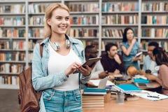 Gruppo di studenti multiculturali etnici in biblioteca Ragazza bianca che per mezzo della compressa Immagini Stock