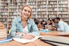 Gruppo di studenti multiculturali etnici in biblioteca Ragazza bianca che prende le note fotografia stock