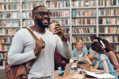 Gruppo di studenti multiculturali etnici in biblioteca Tipo nero con le note ed il caffè Fotografia Stock