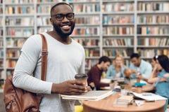 Gruppo di studenti multiculturali etnici in biblioteca Tipo nero con le note ed il caffè Fotografie Stock Libere da Diritti