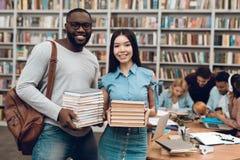 Gruppo di studenti multiculturali etnici in biblioteca Tipo nero e ragazza asial con i libri Immagine Stock