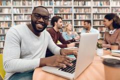 Gruppo di studenti multiculturali etnici in biblioteca Tipo nero sul computer portatile Immagini Stock Libere da Diritti