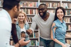 Gruppo di studenti multiculturali etnici che parlano e che ridono nella biblioteca Fotografia Stock Libera da Diritti