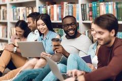 Gruppo di studenti multiculturali etnici che si siedono vicino allo scaffale per libri in biblioteca Fotografie Stock