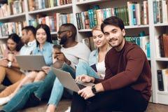 Gruppo di studenti multiculturali etnici che si siedono vicino allo scaffale per libri in biblioteca Fotografia Stock Libera da Diritti