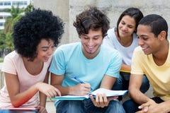 Gruppo di studenti multietnici che imparano all'aperto sulla città universitaria Immagini Stock