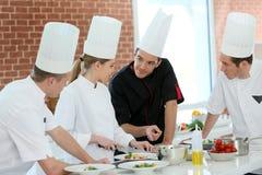 Gruppo di studenti nell'addestramento che cucinano corso Fotografie Stock