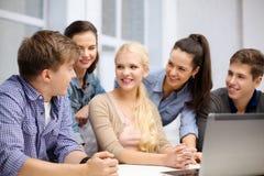 Gruppo di studenti sorridenti con il computer portatile alla scuola Immagine Stock Libera da Diritti