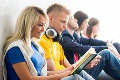 Gruppo di studenti sui libri di lettura della rottura e sugli smartphones usando Fotografia Stock