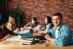 Gruppo di studenti universitari che si siedono alla tavola fotografie stock