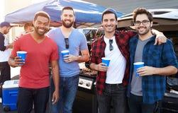 Gruppo di Tailgating maschio dei fan di sport nel parcheggio dello stadio Fotografia Stock