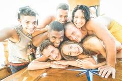 Gruppo di tipi e di ragazze dei migliori amici che prendono selfie al partito della barca Immagine Stock