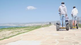 Gruppo di turisti che guidano i motorini elettrici dei segways lungo la spiaggia un giorno ventoso soleggiato Movimento lento archivi video