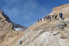 Gruppo di turisti che scalano sul vulcano di Mutnovsky del cratere kamchatka Fotografia Stock