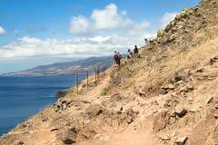 Gruppo di turisti su un'alta costa pietrosa dell'oceano Fotografie Stock