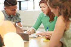 Gruppo di Unposed di imprenditori creativi di affari in un ufficio aperto di concetto che confronta le idee insieme su una compre immagine stock
