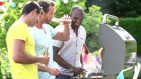 Gruppo di uomini che cucinano sul barbecue a casa archivi video