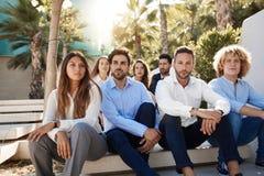 Gruppo di uomini d'affari che si siedono fuori fotografie stock libere da diritti