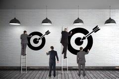 Gruppo di uomini di affari che scrivono sulla parete 3d con gli obiettivi Fotografie Stock Libere da Diritti