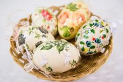 Gruppo di uova di Pasqua variopinte decorate con i fiori fatti dalla tecnica di decoupage, in un canestro fotografia stock libera da diritti