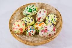 Gruppo di uova di Pasqua variopinte decorate con i fiori fatti dalla tecnica di decoupage, in un canestro immagini stock
