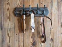 Gruppo di vecchi pattini da ghiaccio bianchi che appendono su una parete di legno Fotografia Stock