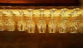 Gruppo di vetri di vino vuoti che appendono sullo scaffale della barra nel fondo d'annata del filtro Fotografia Stock