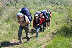 Gruppo di viaggiatore con zaino e sacco a pelo che si alza sulla montagna Fotografia Stock