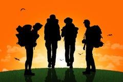 Gruppo di viaggiatori con zaino e sacco a pelo che cammina su una cima di una collina al tramonto Fotografia Stock