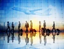 Gruppo di viaggiatori di affari che camminano in un aeroporto Immagine Stock